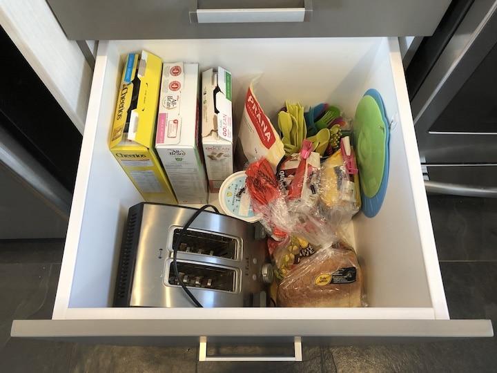 Intérieur d'un tiroir de cuisine avec grille-pain et nourriture pour déjeuners