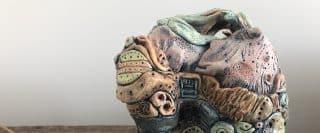 Poterie (vase en poterie sculptée multicolore avec différents motifs par Joan Marilyn Moore Tierney sur table de bois variés)
