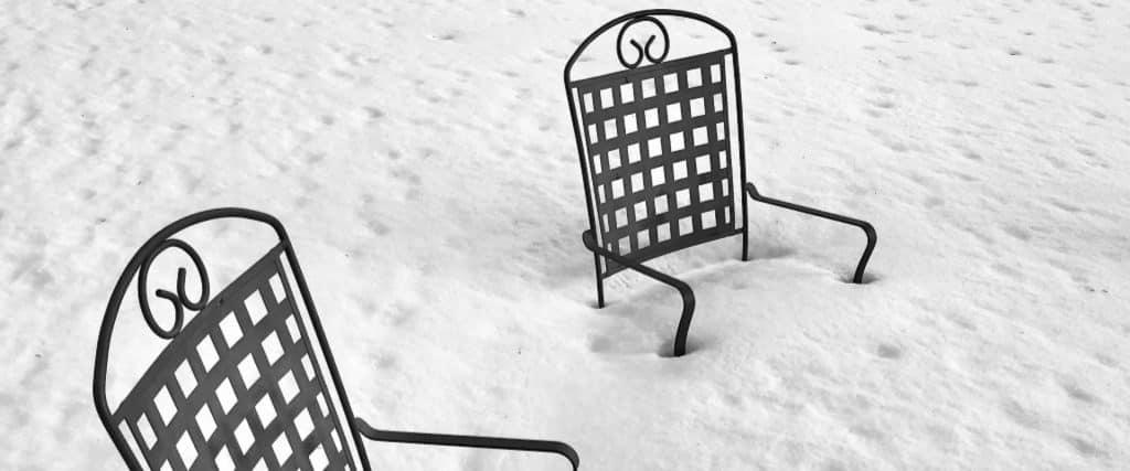 Deux chaises de jardin en métal noir ensevelies sous la neige jusqu'au siège.