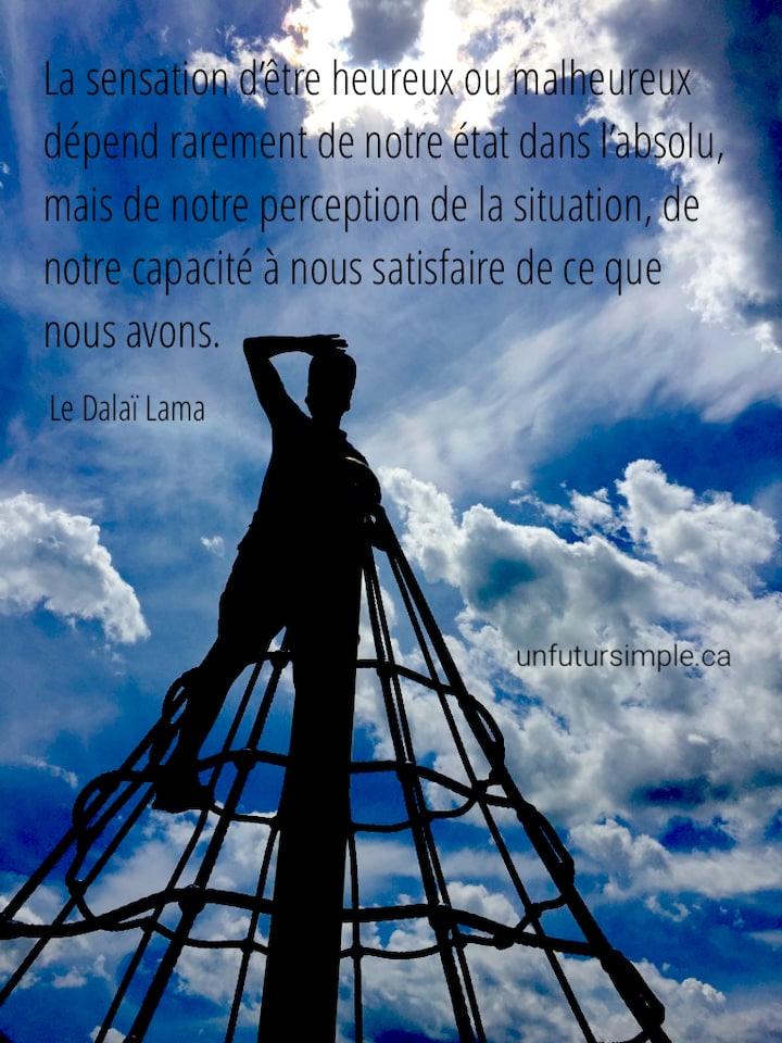 Personne qui regarde vers l'horizon du haut d'une structure de jeu en cordes; citation du Dalaï Lama : La sensation d'être heureux ou malheureux dépend rarement de notre état dans l'absolu, mais de notre perception de la situation, de notre capacité à nous satisfaire de ce que nous avons.
