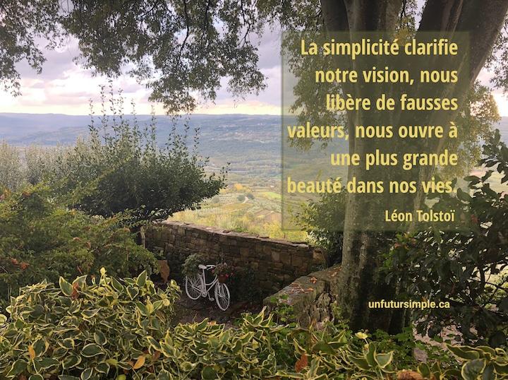 Bicyclette dans un décor de riches verdures avec vue sur une vallée ; citation de Tolstoï : La simplicité clarifie notre vision, nous libère de fausses valeurs et nous ouvre à une plus grande beauté dans nos vies.