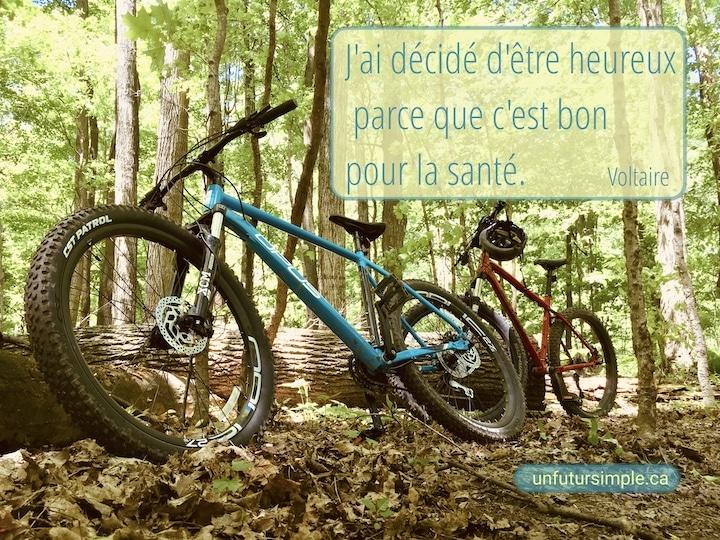 Vélos de montagne bleu et rouge reposant sur un tronc d'arbre dans une forêt; citation de Voltaire : J'ai décidé d'être heureux parce que c'est bon pour la santé.