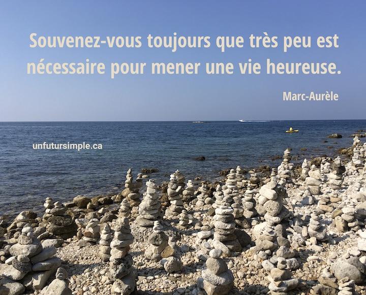 Pierres blanches placées en nombreuses colonnes sur une plage; citation de Marc-Aurèle : Souvenez-vous toujours que très peu est nécessaire pour mener une vie heureuse.