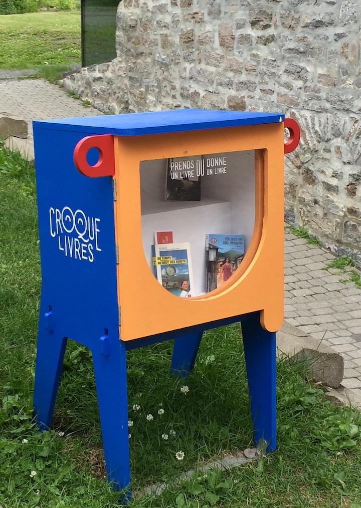 Petite bibliothèque bleue : boîte avec porte vitrée pour échange de livres, près d'une maison en pierre