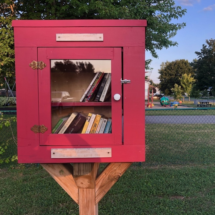 Petite bibliothèque rouge : une boîte avec porte vitrée pour échange de livres, près d'un parc