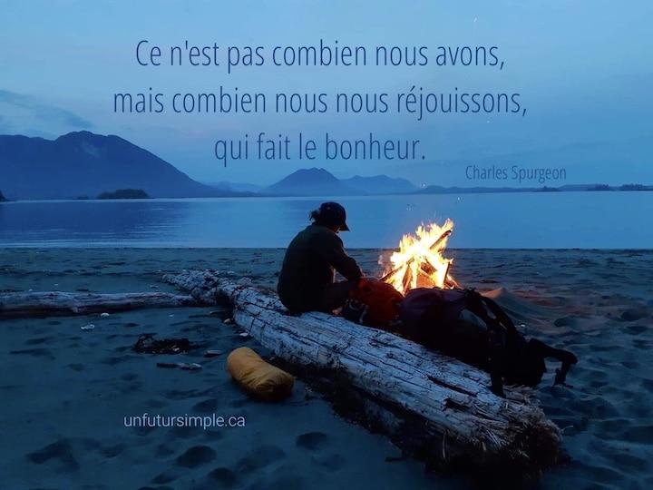Personne assise sur une bûche auprès d'un feu près d'un lac avec citation de Charles Spurgeon : Ce n'est pas combien nous avons, mais combien nous nous réjouissons qui fait le bonheur.