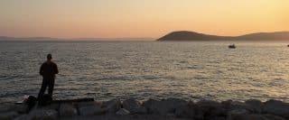 Pêcheur vu de dos devant la mer avec île lointaine au coucher de soleil à Split.