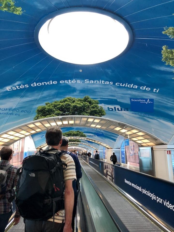 Porter un sac à dos sur un tapis roulant vers la sortie de la gare de Madrid avec publicités au plafond.