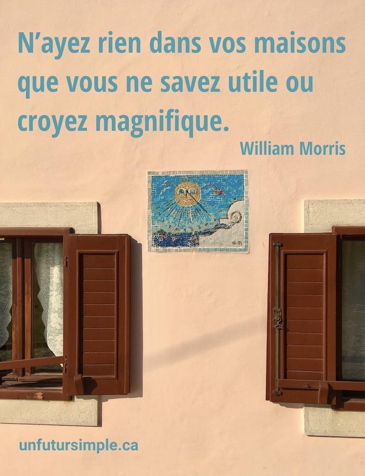Cadran solaire intégré à un mur de maison entre deux fenêtres avec volets; citation de William Morris : N'ayez rien dans vos maisons que vous ne savez utile ou croyez magnifique.
