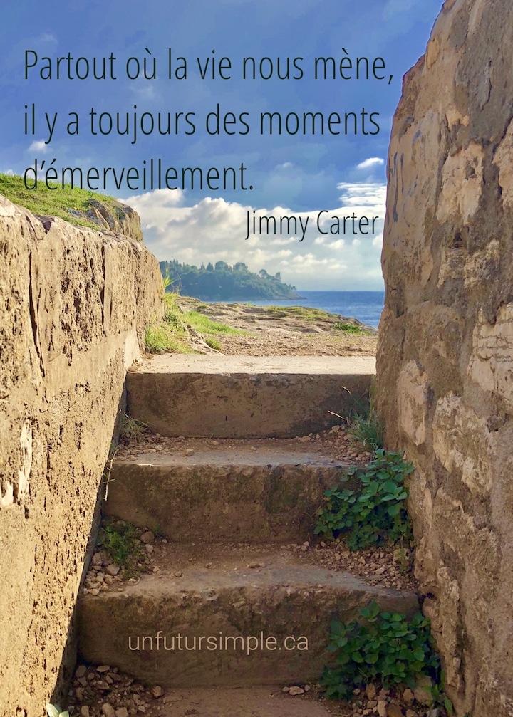 Vue de la côte et l'océan avec en avant-plan des escaliers en pierres encadrés par des murets couleur ocre : Partout où la vie nous mène, il y a toujours des moments d'émerveillement.
