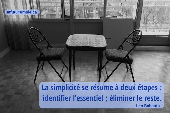 Petite table à carte avec deux chaises pliantes face à face sur un plancher de bois dans une salle à manger devant de grandes fenêtres en noir et blanc; citation de Leo Babauta: La simplicité se résume à deux étapes : identifier l'essentiel; éliminer le reste.