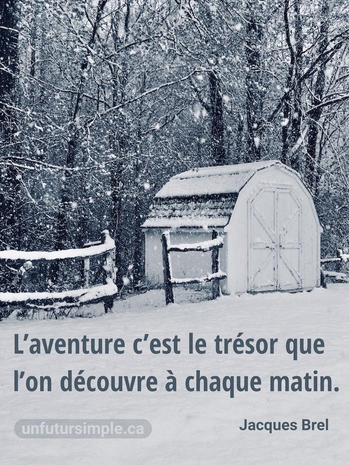 Remise blanche en abord d'une forêt longée d'une clôture de bouts de bois avec de la neige en avant plan et de gros flocons qui tombent; citation de Jacques Brel : L'aventure c'est le trésor que l'on découvre à chaque matin.