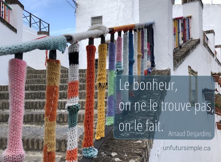 Citation de Arnaud Desjardins : Le bonheur, on ne le trouve pas, on le fait. Arrière-plan: Balustrade d'escalier extérieure enveloppée de tricots multicolores;