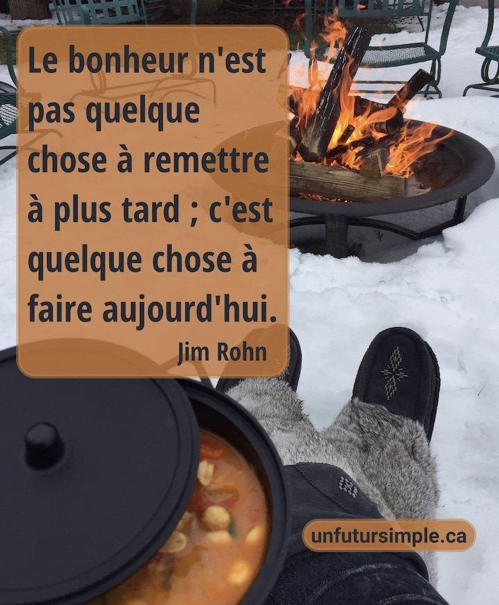 Citation de Jim Rohn : Le bonheur n'est pas quelque chose à remettre à plus tard; c'est quelque chose à faire aujourd'hui. Arrière-plan: Mukluks gris et repas en marmite noire près d'un feu dans la neige.