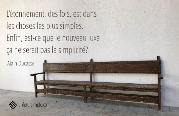 citation de Alain Ducasse: L'étonnement, des fois, est dans les choses les plus simples. Enfin, est-ce que le nouveau luxe ça ne serait pas la simplicité? Arrière-plan: Long banc de bois brun sur fond de mur blanc.