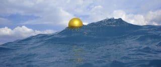 Ballon de couleur or qui flotte sur une vague d'eau bleue foncée et sous un ciel avec nuages blancs.