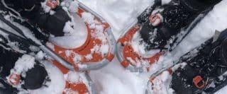 Vue en plongée de trois paires de raquettes Faber avec bottes dans la neige