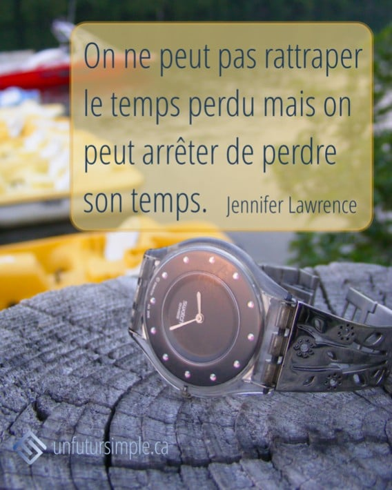 citation de Jennifer Lawrence: On ne peut pas rattraper le temps mais on peut arrêter de perdre son temps. Arrière-plan: Montre sur une bûche de bois avec lac et pédalos en arrière-plan;