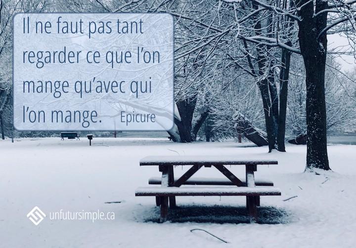 Citation de Épicure: Il ne faut pas tant regarder ce que l'on mange qu'avec qui l'on mange. Arrière-plan: Table de pique-nique en bois couverte de neige dans un parc.