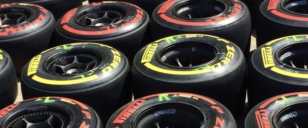 Plusieurs pneus de voitures de course avec lignes jaune et rouge, couchés au sol