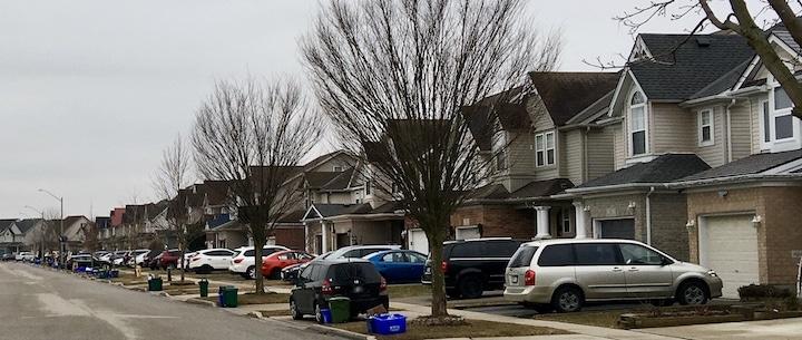 Rue d'un quartier résidentiel avec des voitures devant tous les garages