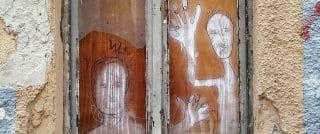 Deux personnages dessinées en graffiti sur une planche de bois dans une fenêtre d'une maison ayant besoin d'entretien.