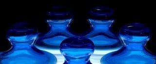 Pions de verre bleu regroupés sur une surface blanche illuminée