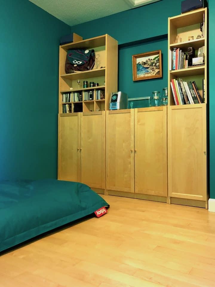 bibliothèque devant mur vert et pouf Fatboy dans pièce flexible