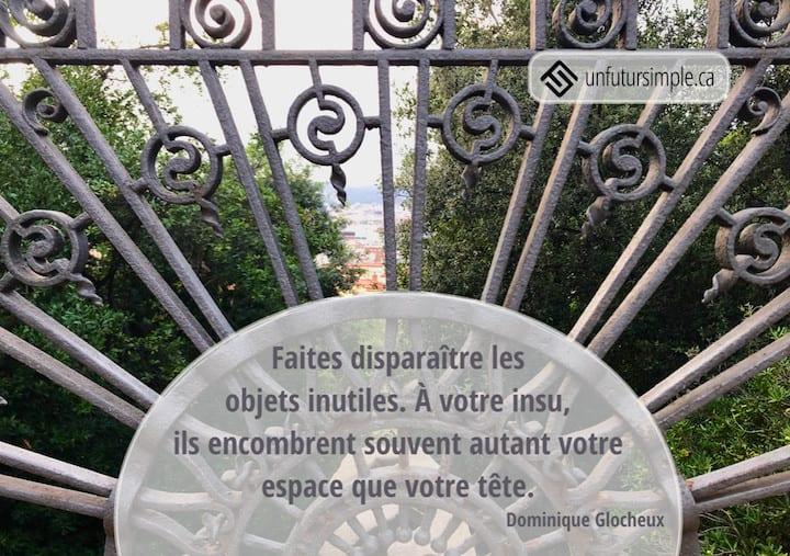 Citation de Dominique Glocheux: Faites disparaître les objets inutiles. À votre insu, ils encombrent souvent autant votre espace que votre tête. Porte de jardin en fer forgé et vue de la ville.
