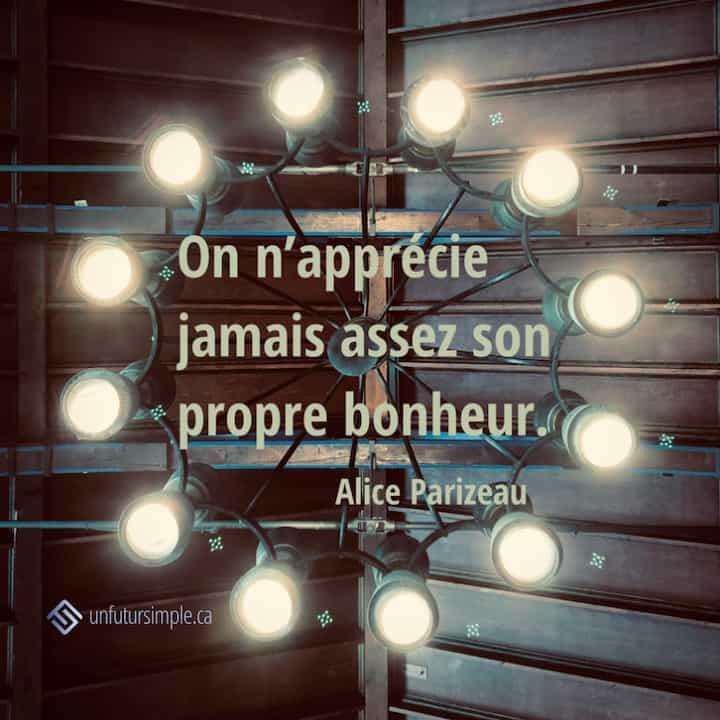 Citation de Alice Parizeau: On n'apprécie jamais assez son propre bonheur. Chandelier suspendu d'un plafond en bois.