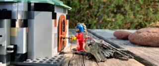 Figurine Lego porte-clés attachée à un trousseau de clés ouvrant la porte d'une maison Lego