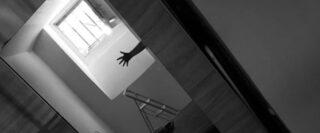 un bras et un escabeau dans un appartement avec prise de vue à angle