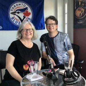 Julie Charland et Michel Gérin dans le studio maison du balado Versus avec le logo des Blue Jays en arrière-plan