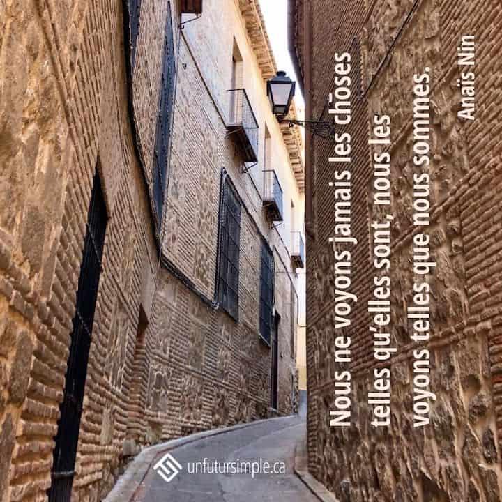 Citation de Anaïs Nin : Nous ne voyons jamais les choses telles qu'elles sont, nous les voyons telles que nous sommes. Route étroite bordée de murs de briques et lanternes à Toledo Espagne.