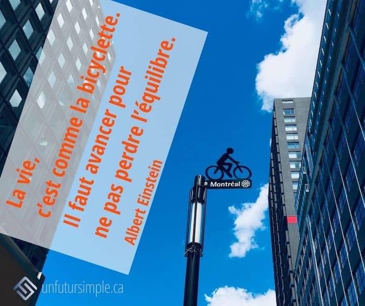 Citation de Albert Einstein : La vie, c'est comme la bicyclette. Il faut avancer pour ne pas perdre l'équilibre. Affiche de rue de Montréal avec un vélo sur fond de ciel bleu entre édifices.