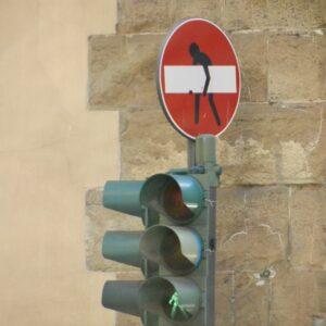 Panneau de sens interdit avec un dessin ajouté d'une personne qui tient la barre blanche