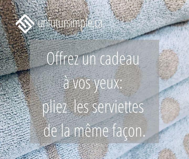 Citation relative à armoire à linge: Offrez un cadeau à vos yeux : pliez les serviettes de la même façon. Arrière-plan: Pile de 4 serviettes de bain bleus avec pois beiges