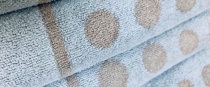 Pile de 4 serviettes de bain bleus avec pois beiges
