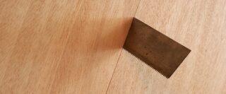 Une scie qui dépasse au-dessus d'une planche de bois.
