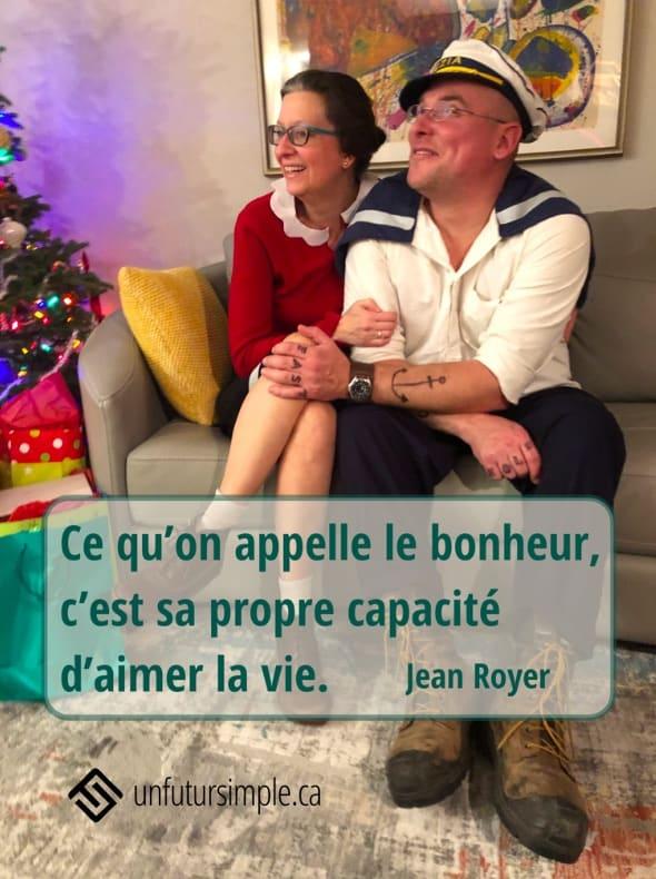 Citation de Jean Royer: Ce qu'on appelle le bonheur, c'est sa propre capacité d'aimer la vie. Arrière-plan: Couple souriant déguisé en Olive Oyl et Popeye assis sur un sofa gris près d'un arbre de Noël.