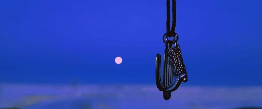 Médaillons en forme de cactus de de botte de cowboy suspendu devant un parebrise de camion avec en arrière-plan la lune rose sur un ciel bleu foncé.