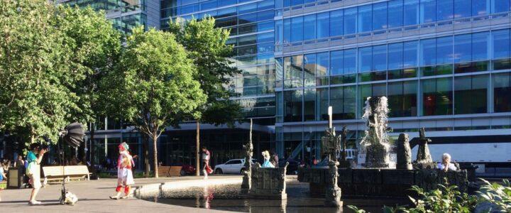 Quelques personnes, certaines déguisées, autour d'une fontaine d'un parc devant un édifice vitré à Montréal.