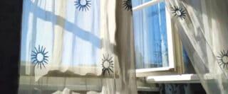 Rideau blanc diaphane avec soleils brodés en bleu ballotant au vent devant une fenêtre ouverte.