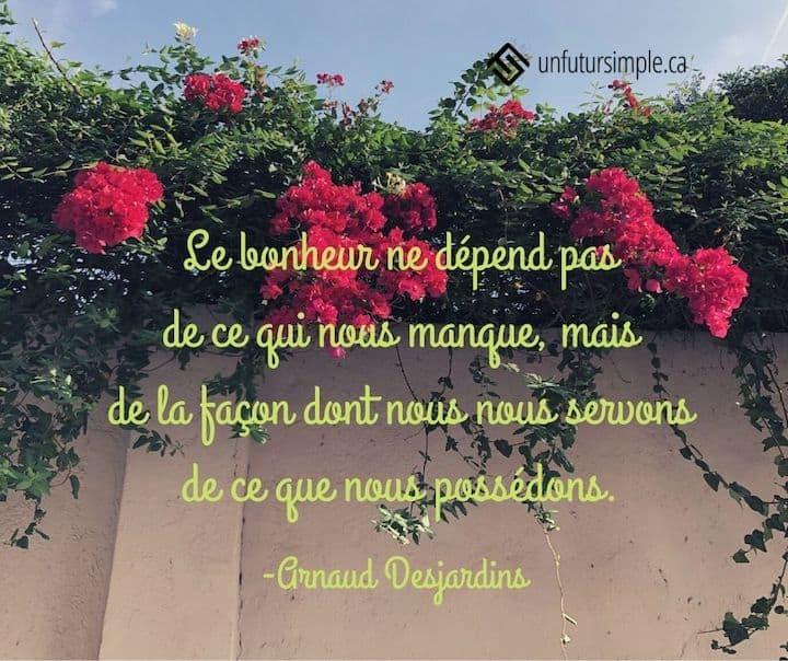 Citation de Arnaud Desjardins : Le bonheur ne dépend pas de ce qui nous manque, mais de la façon dont nous nous servons de ce que nous possédons. Mur beige en contre-plongée avec fleurs rouges et verdure en cascade.