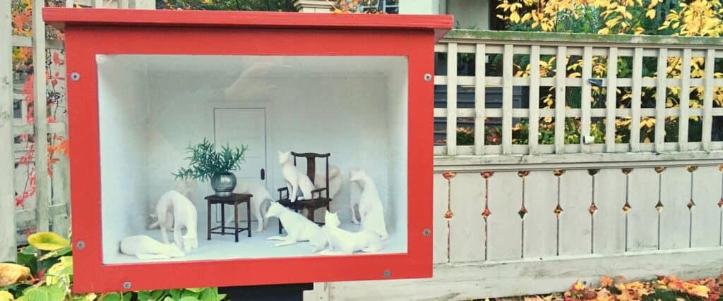 Petite vitrine avec animaux sculptés, à l'extérieur devant une clôture
