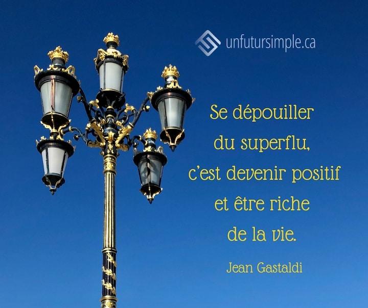 Citation de Jean Gastaldi: Se dépouiller du superflu, c'est devenir positif et être riche de la vie. Lampadaire orné de dorures sur un fond de ciel bleu.