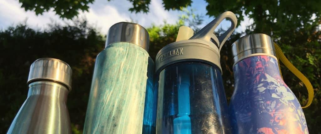 4 bouteilles d'eau en contre-plongée au soleil avec verdure en arrière-plan.