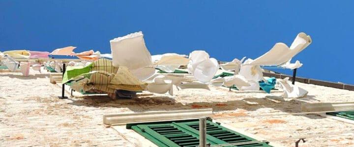 Vêtements qui flottent au vent sur le mur d'une maison sous un ciel bleu.