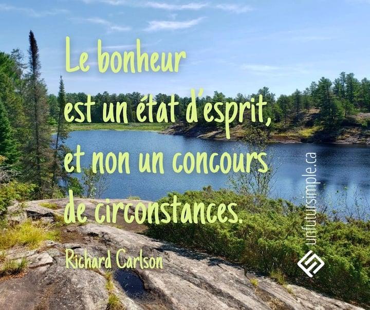 Citation de Richard Carlson: Le bonheur est un état d'esprit, et non un concours de circonstances. Vue d'un lac en Ontario à partir d'un rocher avec des arbres et un ciel bleu.