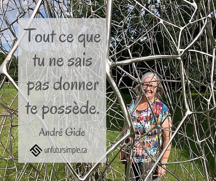 Citation de André Gide: Tout ce que tu ne sais pas donner te possède. Femme souriante derrière une sculpture de métal extérieure donnant l'impression d'une cage.